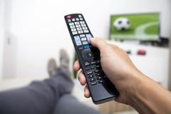 Überwachender Fernsehapparat Fernsteuerungs in der Hand Fußball Stockfoto