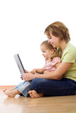 Überwachender Laptop der Frau und des kleinen Mädchens Stockfotos