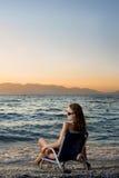 Überwachender Sonnenuntergang der Frau auf dem Strand Stockfotografie