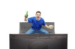 Überwachender Sport des aufgeregten Mannes auf einem Fernsehapparat Stockfoto