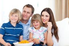 Überwachendes Fernsehen der Familie und essen Chips Stockbilder