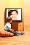 Überwachendes Kino des kleinen Jungen auf Fernsehapparat Stockbilder