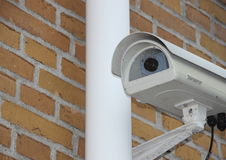 Überwachungskamera-Nahaufnahme angebracht an der gelben Backsteinmauer Lizenzfreies Stockbild