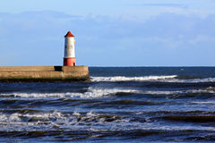 Berwick upon Tweed and harbour and lighthouse. Berwick upon Tweed, in Northumberland, England, showing the harbour wall and the lighthouse at high tide Royalty Free Stock Photos