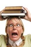 Überwältigte Frau trägt Stapel Bücher auf Kopf Stockfotografie
