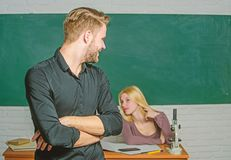 ?berzeugt in seinem Wissen Stehende H?nde des gut aussehenden Mannes kreuzten im Klassenzimmer mit Lehrer M?nnlicher Student mit  lizenzfreie stockbilder