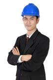 Überzeugte asiatische Arbeitskraft im blauen Schutzhelm und im Gesellschaftsanzug, lokalisiert auf Weiß Stockbilder