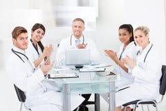 Überzeugte Doktoren, die am Schreibtisch applaudieren Stockfotografie