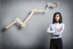 Überzeugte erfolgreiche Geschäftsfrau vor positivem Tendenzdiagramm Stockfotografie