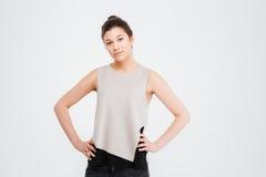 Überzeugte ernste junge Geschäftsfrau, die mit den Händen auf Taille steht Lizenzfreies Stockfoto