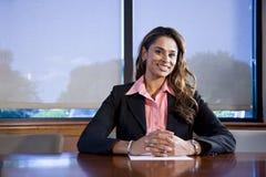 Überzeugte Geschäftsfrau, die im Sitzungssaal sitzt Stockfotos
