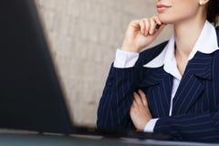 Überzeugte Geschäftsfrau mit Laptopnahaufnahme Stockfoto