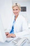 Überzeugte Ärztin unter Verwendung des Computers in der Klinik Stockbild