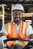 Überzeugter Industriearbeiter, der Gabelstapler am Arbeitsplatz fährt Lizenzfreies Stockbild