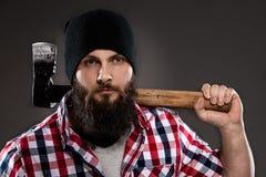 Überzeugter junger bärtiger Holzfällermann, der eine Axt trägt Stockfotografie