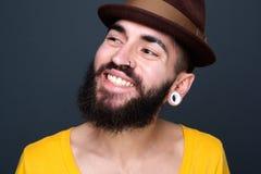 Überzeugter junger Mann mit dem Bartlächeln Stockbild