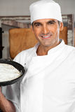 Überzeugter männlicher Bäcker Holding Dough Tray At Bakery Lizenzfreie Stockfotos