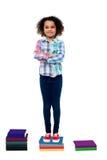 Überzeugtes Schulkind, das auf Büchern steht Stockfoto
