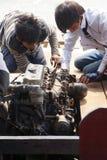 Besättningen arbetar på motorn Arkivfoto