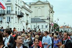 Besök av de kungliga paren i Warszawa Folk som rymmer Union Jack flaggor och blommor Fotografering för Bildbyråer