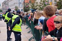 Besök av de kungliga paren i Warszawa Folk som rymmer Union Jack flaggor och blommor Royaltyfri Foto