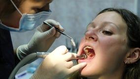 Besöka till tandläkaren som Orthodontist borrar och korrigerar lappskyddsremsan arkivfilmer