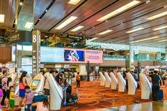 Besökare går runt om avvikelsen Hall i den Changi flygplatsen Singapore Arkivfoton