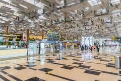 Besökare går runt om avvikelsen Hall i den Changi flygplatsen Singapore Royaltyfria Foton