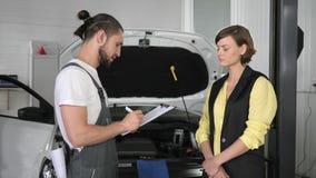 Besökare i auto reparation, tjänste- bok i den auto mekanikern för hand, pro-grabb lager videofilmer