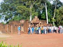 Besökare som framme samlar av på ingången av den Banteay Srey eller Banteay Srei templet i Cambodja Arkivfoton