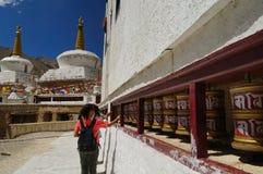 Besökare som roterar bönekvarnen på den Lamayuru kloster i Ladakh, Arkivfoto