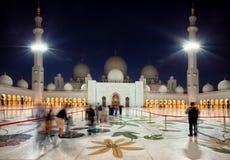 Besökare som skriver in den storslagna moskén av Zayed i Abu Dhabi av emirater på skymning Royaltyfri Foto