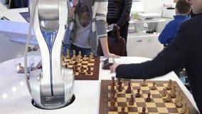 Besökare som spelar robotschack i modig mitt lager videofilmer