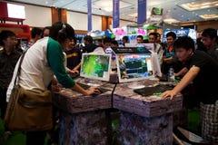 Besökare som spelar videospel på Indo den modiga showen 2013 Arkivbilder