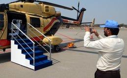 Besökare tar fotoet med mobiltelefonhelikopterutställningen Arkivbild