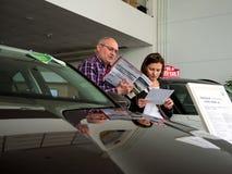 Besökare till bilåterförsäljaren lär prislistor för nya bilar Royaltyfri Fotografi