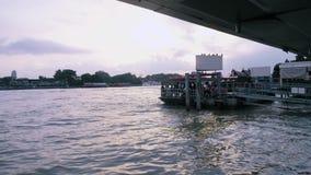 Besökare under skymning på pir på den Chao Phraya floden i Bangkok, Thailand lager videofilmer