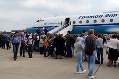 Besökare undersöker nivån Yak-40 på det internationella flyget och gör mellanslag salongen MAKS-2013 Royaltyfri Fotografi