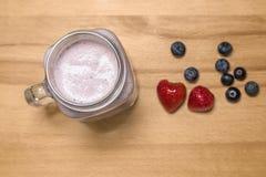 Bes smoothie in een metselaarkruik met aardbei en bosbessen  stock fotografie