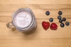 Bes smoothie in een metselaarkruik met aardbei en bosbessen  royalty-vrije stock afbeelding