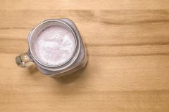 Bes smoothie in een metselaarkruik op een houten scherpe raad de bovenkant wedijvert royalty-vrije stock foto