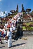 Besakih,巴厘岛/印度尼西亚村庄-大约2015年10月:人们从祈祷回来在Pura Besakih寺庙 库存图片