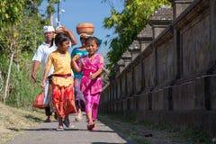 Besakih,巴厘岛/印度尼西亚村庄-大约2015年10月:愉快的家庭从节日回来在Pura Besakih 库存照片