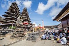 Besakih,巴厘岛/印度尼西亚村庄-大约2015年10月:祈祷在Pura Besakih巴厘语寺庙的人们 免版税库存照片