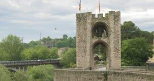 Besalu, Girona, Cataluña, España Puente Románico medieval viejo de Besalu de la señal famosa sobre el río de Fluvia en nublado almacen de video