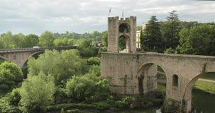 Besalu, Girona, Cataluña, España Puente Románico medieval viejo de Besalu de la señal famosa sobre el río de Fluvia en nublado metrajes