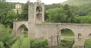 Besalu, Girona, Cataluña, España Puente Románico medieval viejo de Besalu de la señal famosa sobre el río de Fluvia en nublado almacen de metraje de vídeo