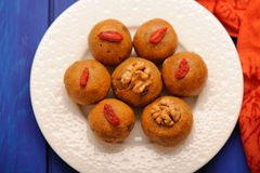 Besan laddu, vegan Indian sweets with wallnuts and goji berries. On deep blue table top view royalty free stock image