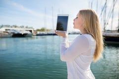Besando al adolescente con la tableta digital al aire libre Foto de archivo