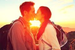 Besando los pares románticos en la puesta del sol Imágenes de archivo libres de regalías